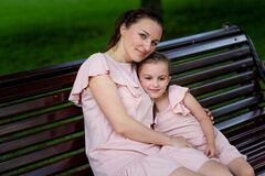 Mother and daughter 5-6 years old walk in the Park in the summer, mother hugs her daughter sitting on a bench, the concept of a