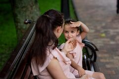 Mother and daughter 5-6 years old walking in the Park in the summer, mother talking to her daughter sitting on a bench, the