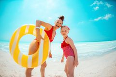 Mother and daughter with yellow inflatable lifebuoy on beach stock photo