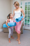 Mother and daughter with yoga mats. At home in the living room Royalty Free Stock Photography