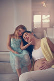Mother and daughter. Young pregnant women and her daughter have a moment of tenderness Stock Photo