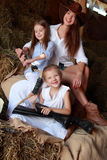Mother and daughter. Young mother with two daughters sitting on hay ranch in the American stock photography