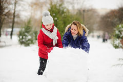 Mother with daughter of younger school age build a snowman in the yard. Royalty Free Stock Photo