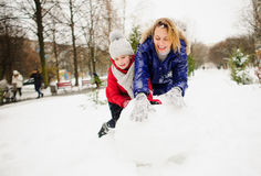 Mother with daughter of younger school age build a snowman in the yard. Royalty Free Stock Images