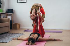 Mother and daughterdoing gymnastic exercises together at home Stock Photos
