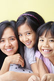 Mother and daughters. Posing together on bed Stock Photo