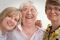 Mother and daughters. An elderly mother and her happy daughter s together in the living room at home Stock Photography