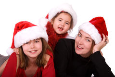 Mother and daughters. Christmas portrait of a mother with her two daughters, all of them are wearing Santa hats. White background Royalty Free Stock Photography