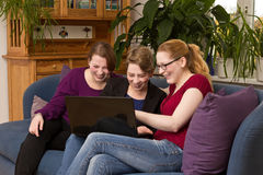 Mother and daughters amused with laptop. Mother and two daughters sitting with laptop on sofa enjoying themselves stock images