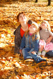 Mother and daughters in autumn leaves Stock Photography