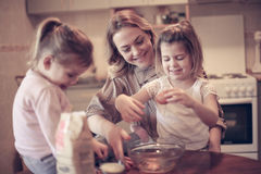 Mother and daughters baking. Mother and daughters baking cookies in kitchen Royalty Free Stock Images