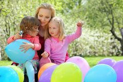 Mother, daughters and balloons in spring Royalty Free Stock Photos