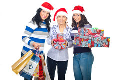 Mother and daughters with Christmas gifts. Mother with two daughters wearing Santa hats and holding Christmas gifts isolated on white background Royalty Free Stock Photography
