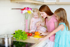 Mother and daughters cooking dinner Stock Image