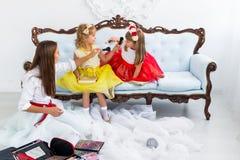Mother and daughters doing makeup Stock Photos