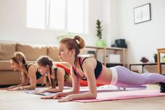 Mother and daughters doing plank exercise at home. Mother and daughters doing plank exercise at home royalty free stock image