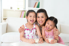 Mother and daughters drinking milk. Happy Asian mother and daughters drinking milk at home. Parent and children. Beautiful family model Stock Image