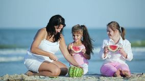 Mother and daughters eat watermelon by the sea stock footage