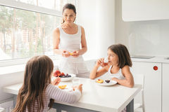 Mother and daughters enjoying a delicious fruit dessert stock photography