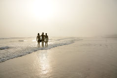Mother and daughters enjoying time together on a foggy beach. Royalty Free Stock Photography