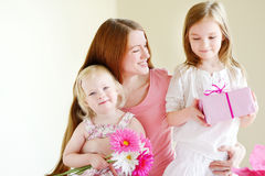 Mother and he daughters giving a gift Royalty Free Stock Image