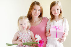 Mother and he daughters giving a gift Stock Images