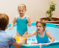 Mother and  daughters having fun in pool. Mother and little daughters having fun in pool outdoor Royalty Free Stock Photography