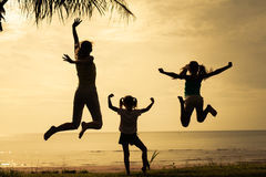 Mother and  daughters jumping at the beach Stock Photography