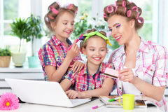 Mother and daughters  with laptop. Portrait of happy  Mother and little daughters in hair curlers with laptop  at home Royalty Free Stock Photos