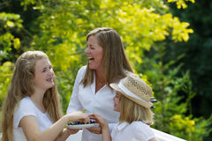 Mother and daughters laughing while eating berries outside Stock Images
