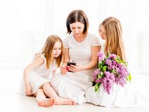 Mother with daughters looking at smartphone Royalty Free Stock Photo