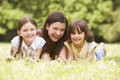 Mother and daughters lying outdoors with flower Stock Image