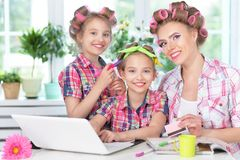 Mother and daughters making hairstyles. Mother and daughters sitting at table with laptop and making hairstyles Stock Photography