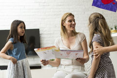 Mother with daughters. Mum with daughters looking at their drawings at home stock photos