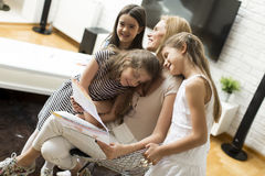 Mother with daughters. Mum with daughters looking at their drawings at home royalty free stock images