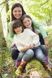 Mother and daughters outdoors in woods sitting Stock Photo