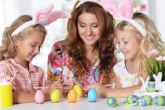 Mother with daughters paint eggs Royalty Free Stock Image