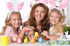 Mother with daughters paint eggs Royalty Free Stock Photos