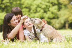 Mother and daughters in park with dog smiling Royalty Free Stock Photography