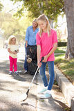 Mother And Daughters Picking Up Litter In Suburban Street Royalty Free Stock Photography