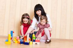 Mother and daughters play with bright toys Stock Images