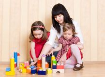 Mother and daughters play with toys Stock Photos