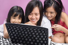 Mother and daughters playing with laptop. Asian mother and daughters playing with laptop in the bedroom Stock Image