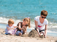 Mother and daughters playing in the sand Stock Photos