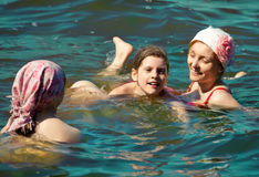 Mother and daughters playing in the sea Stock Images
