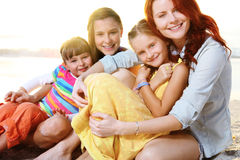 Mother and daughters playing at the sunny beach. Royalty Free Stock Photography