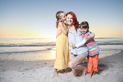 Mother and daughters playing at the sunny beach. Royalty Free Stock Photo