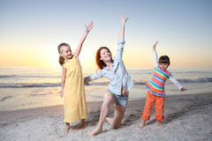 Mother and daughters playing at the sunny beach. Royalty Free Stock Photos