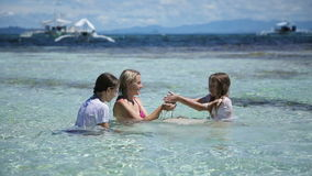 Mother and daughters playing in the tropical sea stock footage