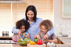 Mother and daughters preparing salad in the kitchen together Royalty Free Stock Photo
